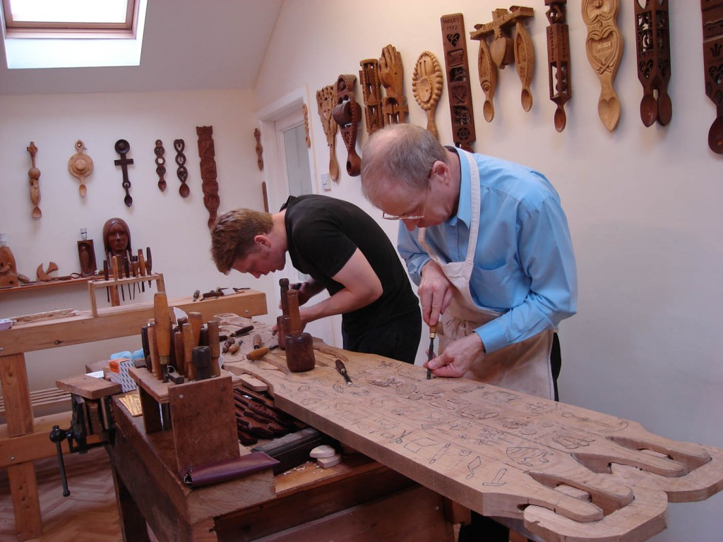 Photo of two men carving traditional Welsh lovespoons