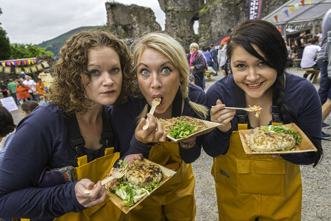 Three women eating at a Food Festival