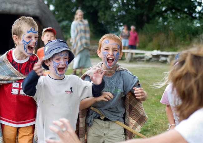 3 boys with blue celtic style painted faces having fun at Castell Henllys