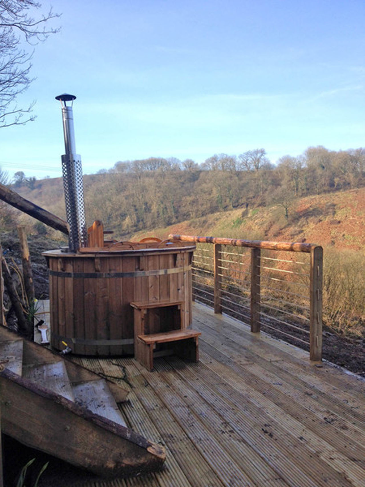 woodfired hot tub sat on wooden decking area in the countryside