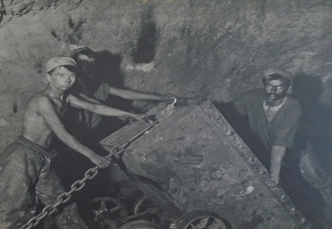 3 young men/boys working in a mine inear the Cambrain Mountains when it was operational