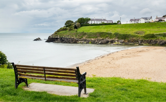 bench overlooking north beach at aberporth with village green opposite and a few white properties