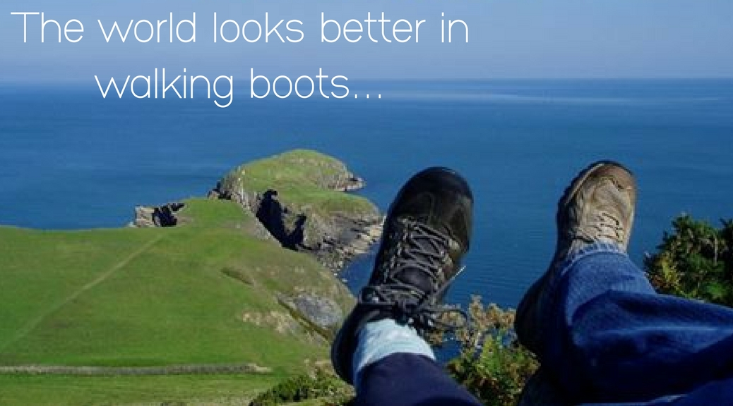 people show their walking boots on the top of a hill above a beautiful view of the coast