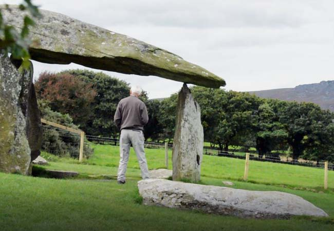 Pentre Ifan Burial Chamber with an elederly man standing underneath the rocks