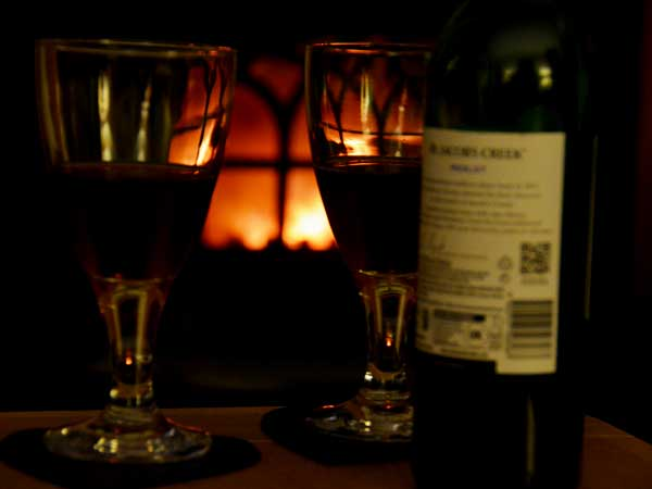two glasses of red wine beside a bottle infront of a roaring fire at Cryngae Farmhouse