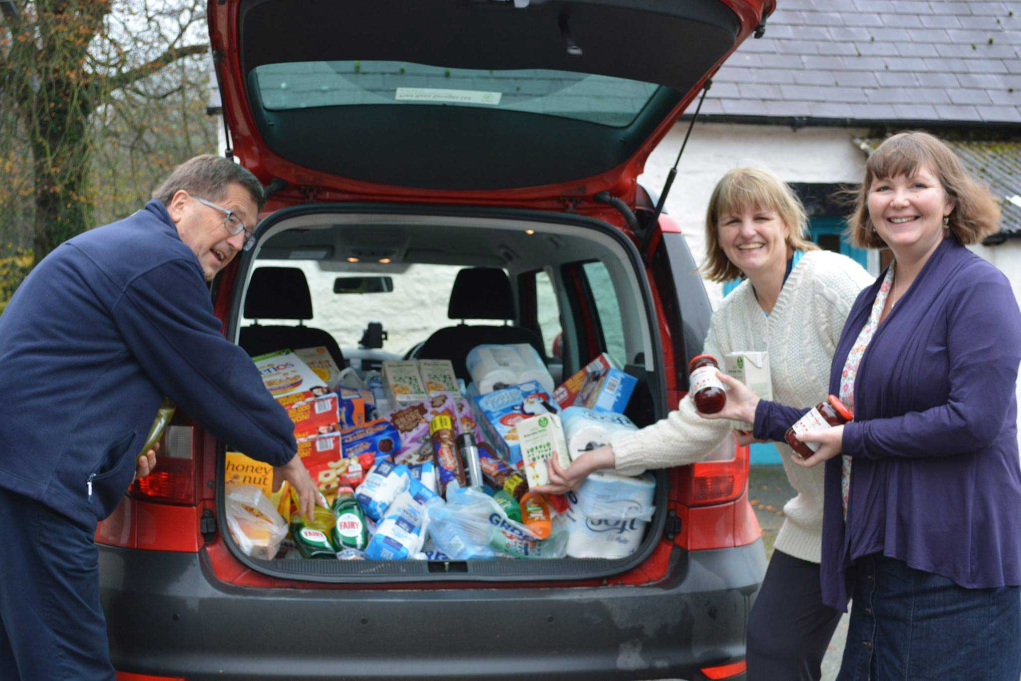 Staff and Senior Partmer of West Wales Holiday Cottages loading items for Cardigan Foodbank into the boot of a car